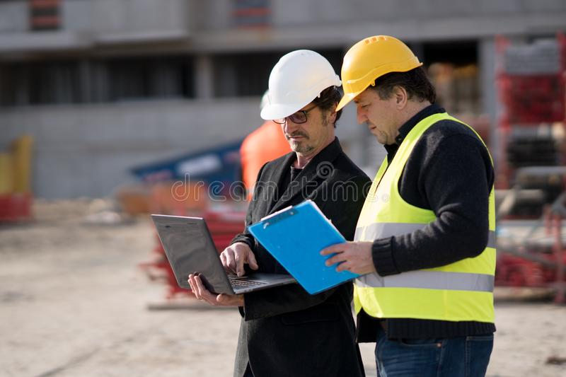 Civil engineer giving instructions to construction worker. Civil engineer giving instructions to a construction worker using a computer laptop. Outdoors stock photography