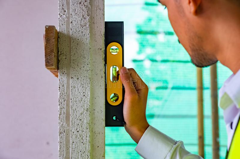 Engineer is checking wall level in building site stock image