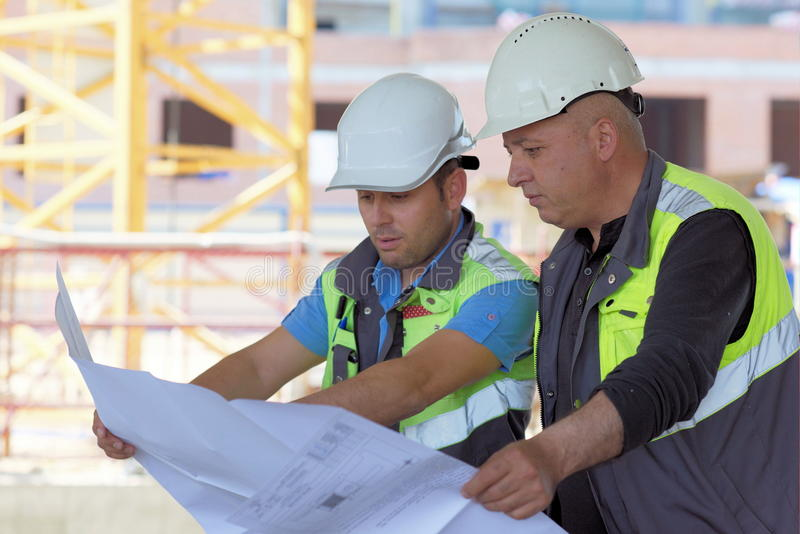 Civil Engineer And Senior Foreman At Construction Site. Are inspecting ongoing production according to design drawings stock photography