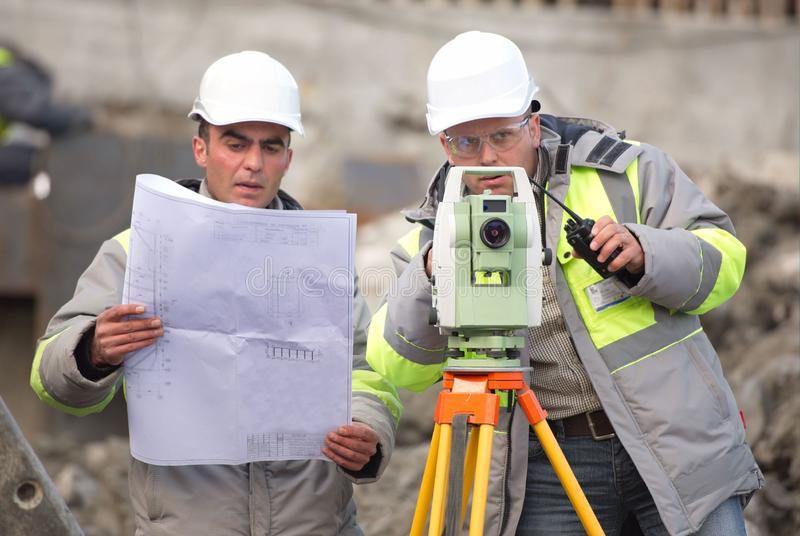 Civil Engineer and Surveyor At Consruction Site. Civil Engineer and Surveyor at at construction site are inspecting ongoing production according to design royalty free stock photo