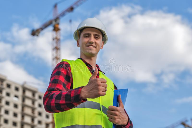 Civil engineer in a white helmet on the background of construction, with a raised thumb royalty free stock photography
