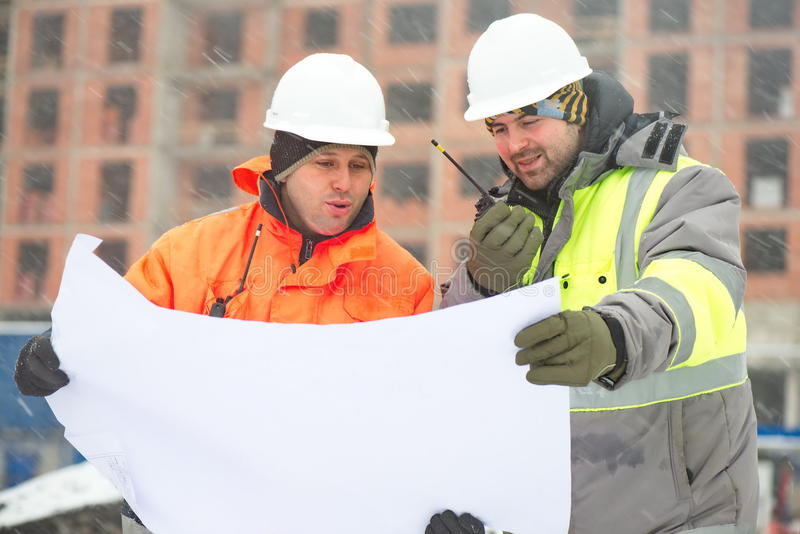 Civil engineers at construction site in winter season royalty free stock photo