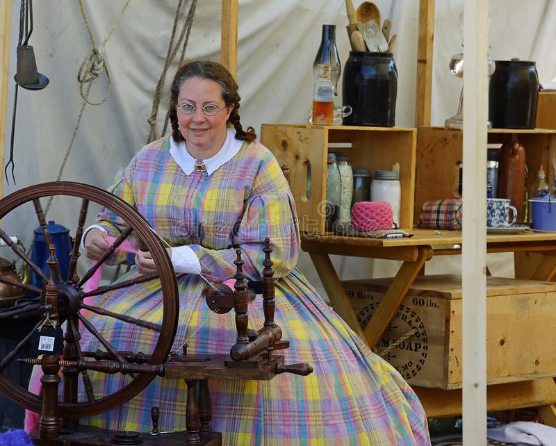 Holland Michigan, USA - September 2017: Civil War Reenactment woman seemstress. A civil war reenactment person at a spinning wheel making homemade clothing in stock image