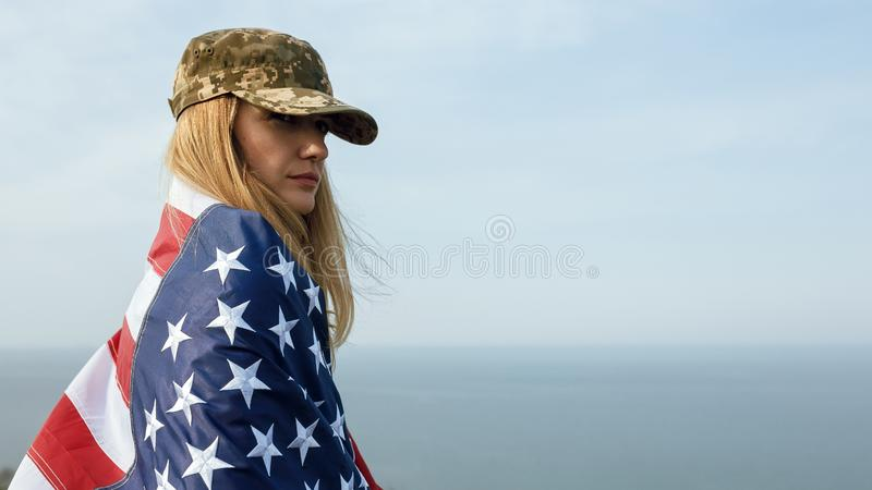 Civilian woman in her husband`s military cap. A widow with a flag of the united states left without her husband. Memorial Day to. Fallen soldiers in the war royalty free stock image