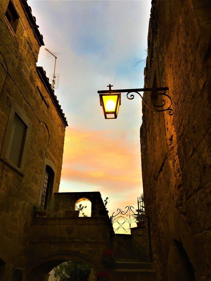 Civita di Bagnoregio, Provinz von Viterbo, Italien Alte Stadtecke, -lampe und -sonnenuntergang stockfotografie