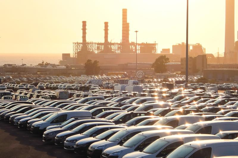 Civitavecchia, Italy. New cars on the parking in industrial zone. Thermoelectric coal-fired power station in background. royalty free stock images
