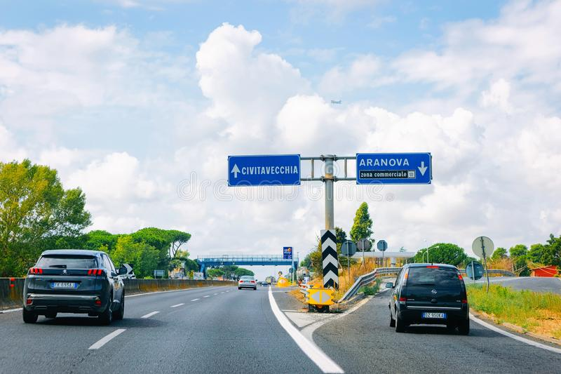 Cars and blue traffic signs to Civitavecchia and Aranova in the road in Italy. Civitavecchia, Italy - September 7, 2017: Cars and blue traffic signs to stock photos