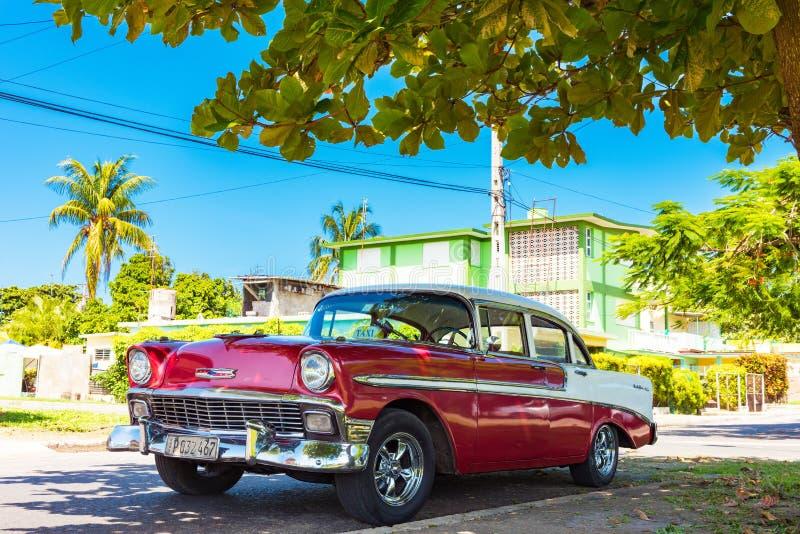 Clásico blanco rojo americano 1956 Chevrolet Bel Air aparcamiento debajo de las palmas en la calle secundaria adentro foto de archivo libre de regalías