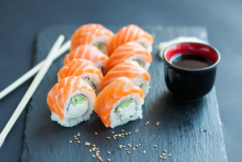 Clássico do rolo de Philadelphfia em um fundo de pedra escuro Salmões, queijo de Philadelphfia, pepino, abacate Sushi japonês fotografia de stock royalty free