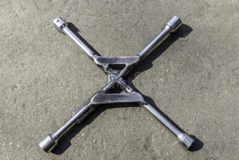 Clé à roues sur l'asphalte avec 4 extrémités photos stock