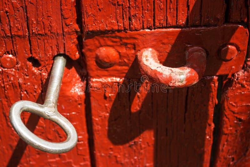 Clé antique de fer de la porte dans la vieille porte en bois rouge images libres de droits