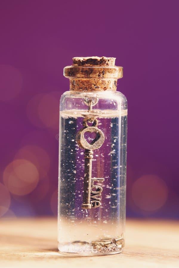 Clé d'amour à l'intérieur de la bouteille de verre miniature photos stock