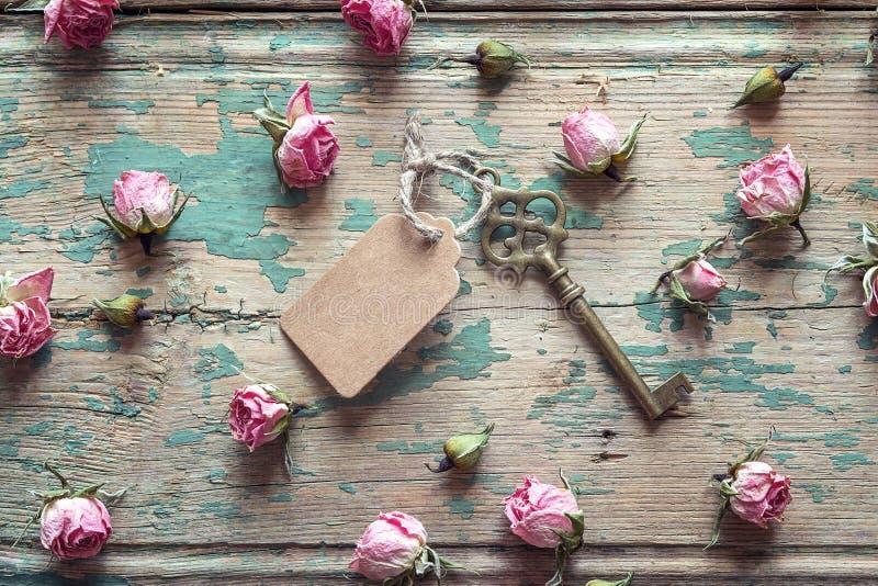 Clé de vintage avec une étiquette et petites roses roses sur un vieil en bois image stock