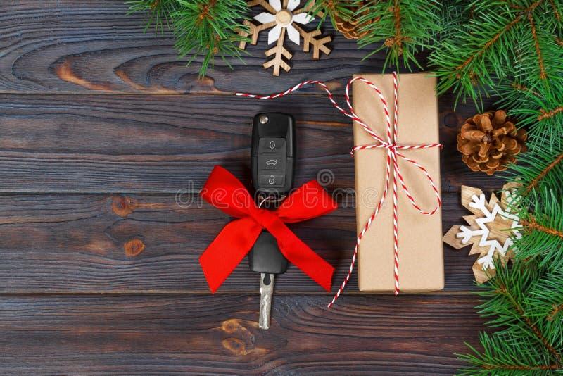Clé de voiture avec l'arc coloré avec le boîte-cadeau sur le fond en bois photos stock