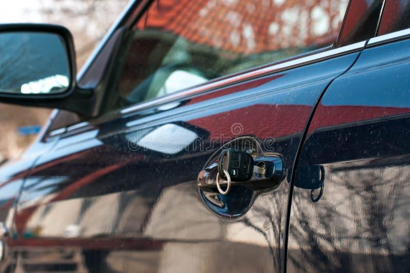 Clé de voiture sur la portière de voiture bleue moderne photographie stock