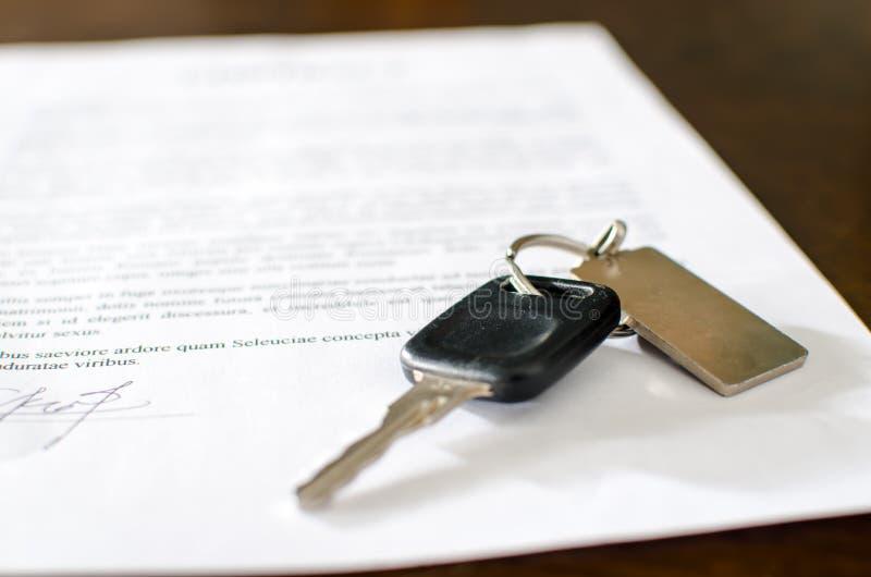 Clé de voiture sur un contrat de ventes signé images libres de droits