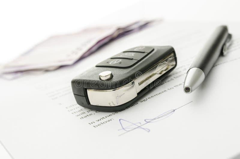 Clé de voiture sur un contrat de vente de voiture photo stock