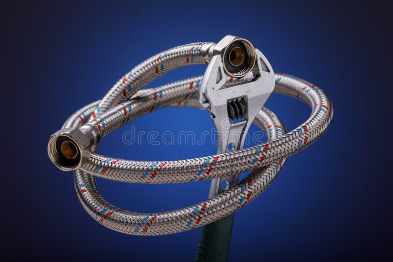 Clé réglable avec le tuyau flexible sur le fond bleu photos stock