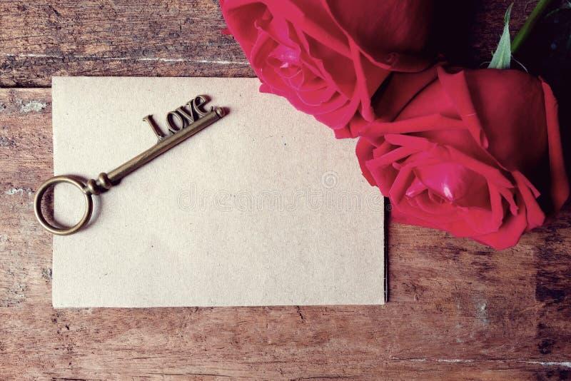 Clé rouge de forme d'alphabet de rose et d'amour avec la carte de papier sur le plancher en bois Rétro simulation de couleur photo stock