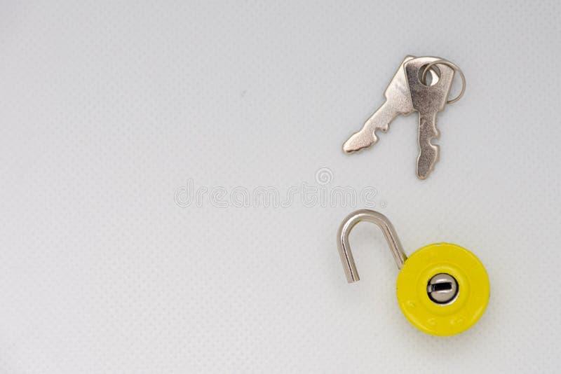 Clés argentées et un cadenas débloqué jaune sur un fond blanc d'isolement image libre de droits