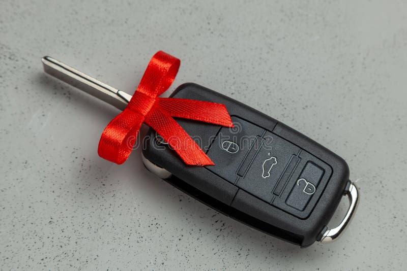 Clés de voiture comme cadeau attaché avec le ruban rouge avec l'arc sur le fond gris image libre de droits
