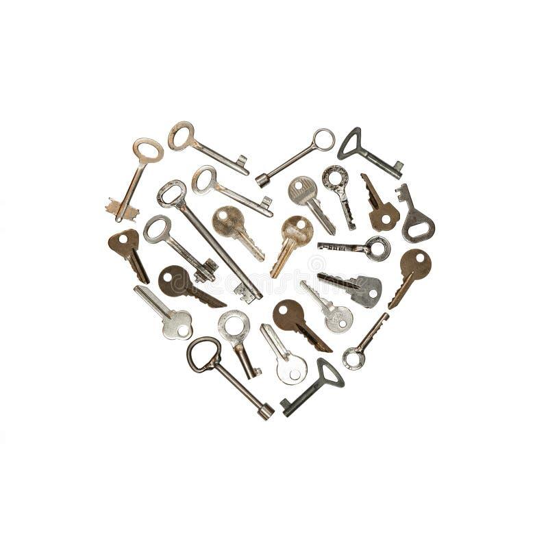 Clés en métal sur la forme blanche de coeur Photographie conceptuelle La cl? est du coeur image libre de droits