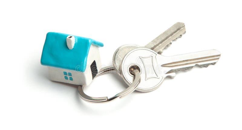 Clés et porte-clés à la maison d'isolement sur le fond blanc Concept d'acheter une maison, louant, hypothèque images libres de droits