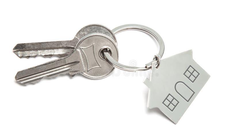 Clés et porte-clés à la maison d'isolement sur le fond blanc Concept de maison de achat image libre de droits