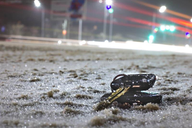 Clés perdues de voiture sur la route en poudre avec la première neige la nuit Sur le fond brouillé image libre de droits