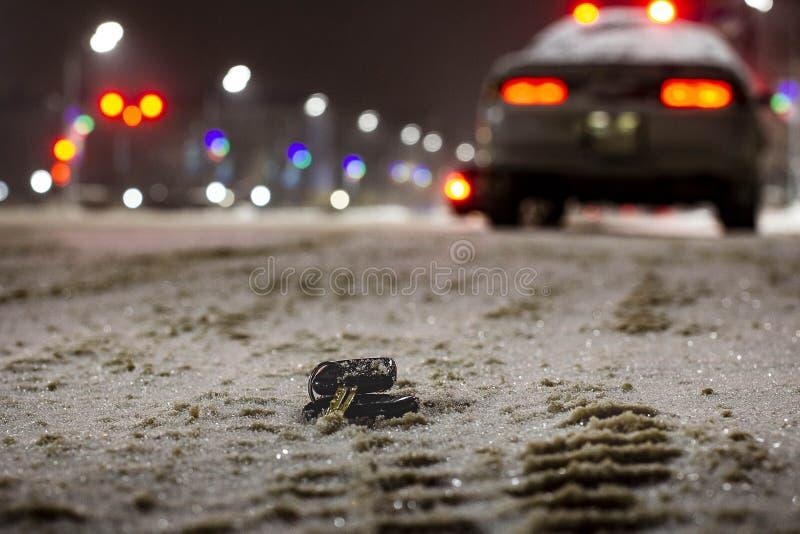 Clés perdues de voiture sur la route en poudre avec la première neige la nuit Sur le fond brouillé photo libre de droits