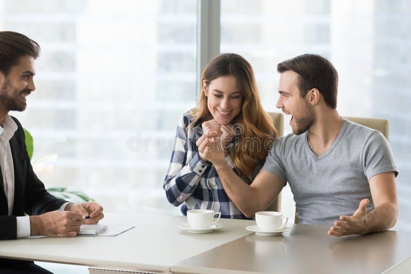 Clés se tenantes heureuses enthousiastes de mari et d'épouse à la nouvelle maison photographie stock
