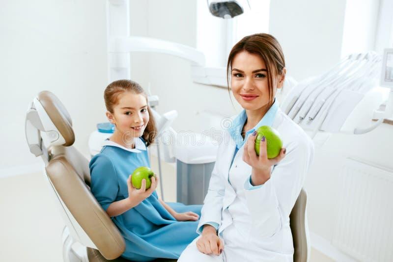 Clínica dental Dentista de sexo femenino And Little Patient que come Apple imágenes de archivo libres de regalías