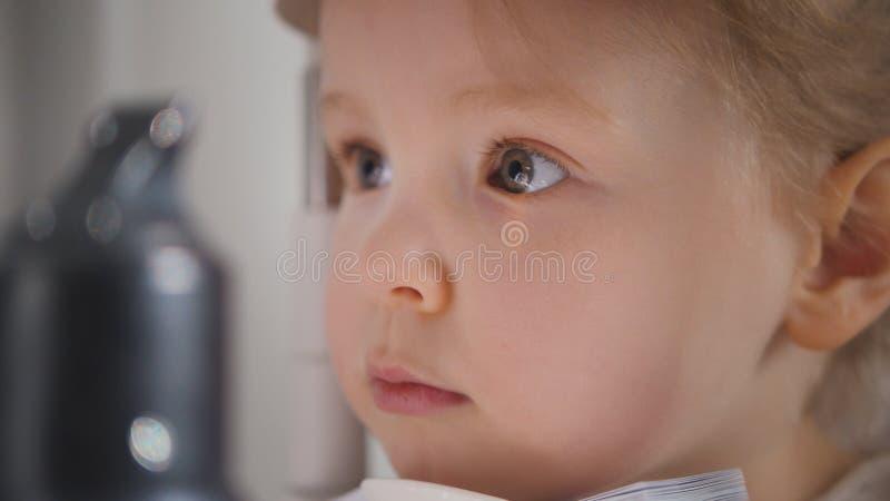 Clínica para crianças - menina loura pequena da oftalmologia do diagnóstico do optometrista imagens de stock royalty free