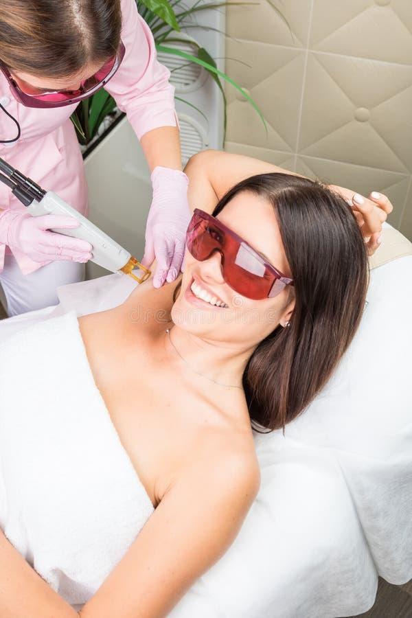 Clínica sonriente de la cosmetología del cliente que tiene retiro del pelo del laser del axila Cliente sonriente hermoso de la mu foto de archivo libre de regalías
