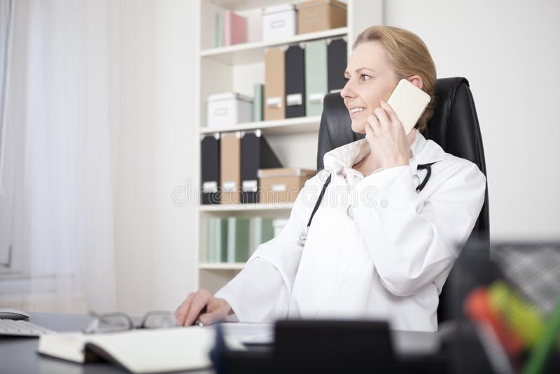Clínico de sexo femenino feliz que invita al teléfono móvil imagen de archivo libre de regalías