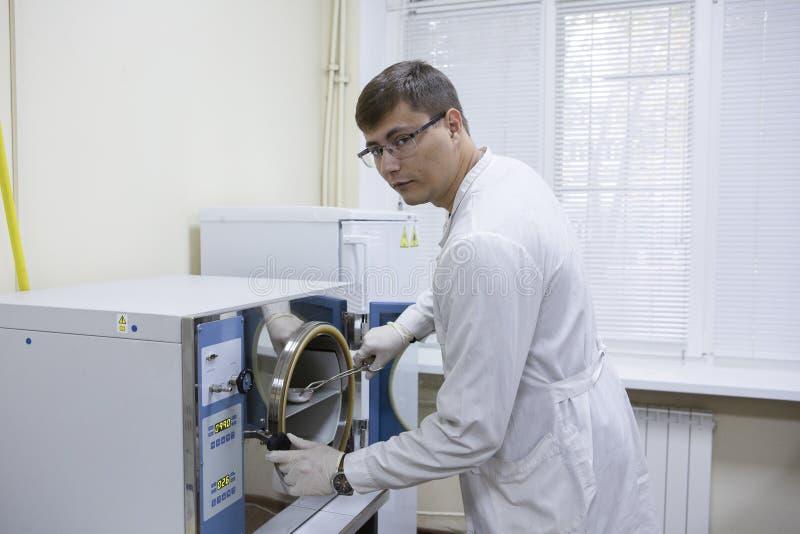 Clínico serio que estudia el elemento químico en el ambiente de trabajo fotografía de archivo