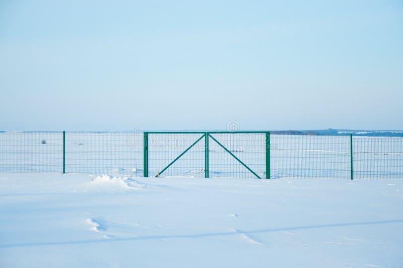 Clôture dans le domaine en hiver photographie stock