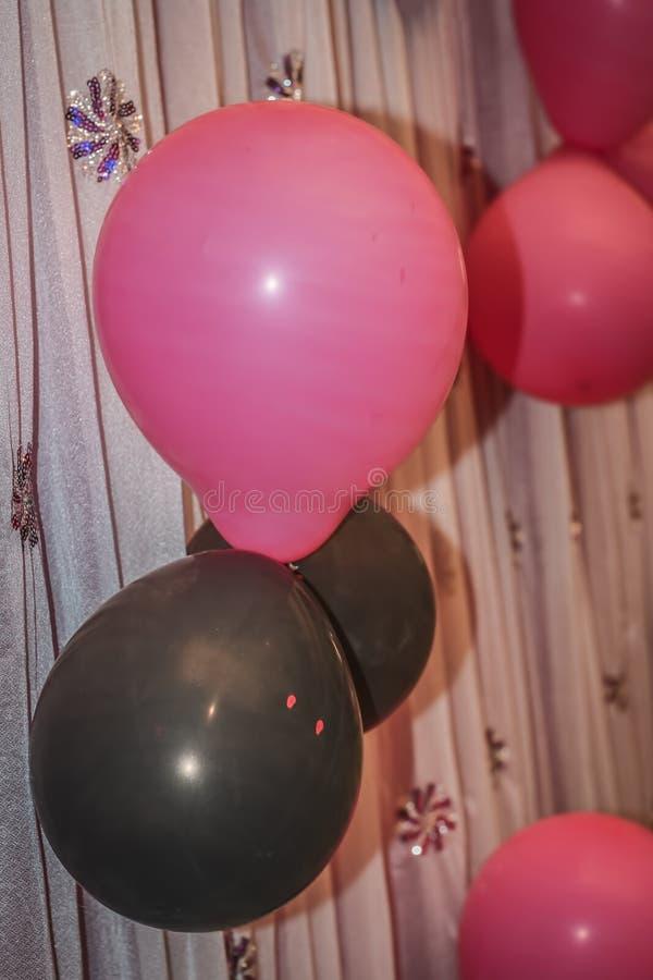 Cl?turez de trois ballons de couleurs i E Noircissez avec le signe de danger, blanc et rose sur un tissu Concepts de c?l?brer cha photos libres de droits