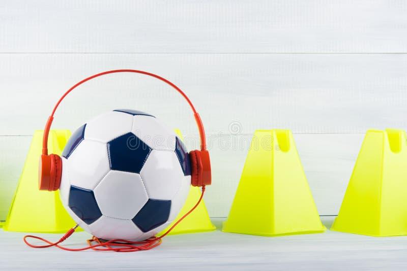 Clôturez les cônes jaunes sur un fond gris, derrière un ballon de football, qui utilise les écouteurs rouges photo stock