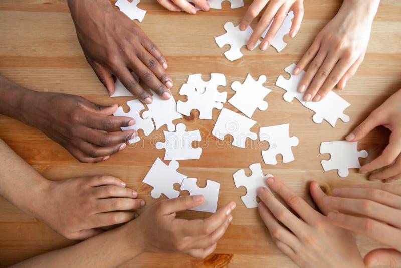 Clôturez supérieur au-dessus des mains diverses de vue assemblant des puzzles photo libre de droits