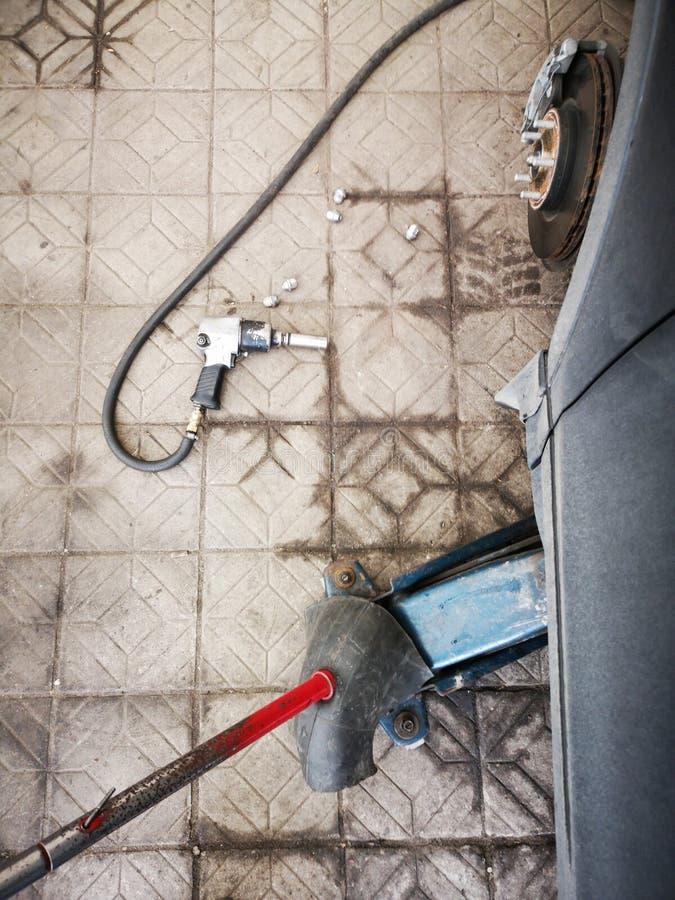 Cl? pneumatique avec des ?crous de pneu de voiture sur de plancher l'ascenseur de cric concret de voiture de c?t? et un morceau d photo stock