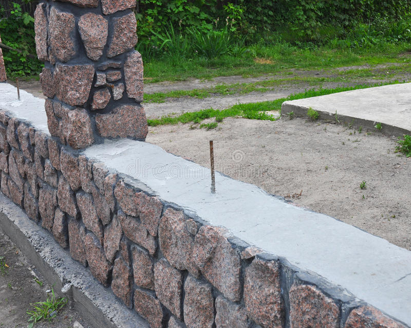 clôture Barrière de granit de bâtiment avec la pierre sauvage criquée décorative de conception photographie stock