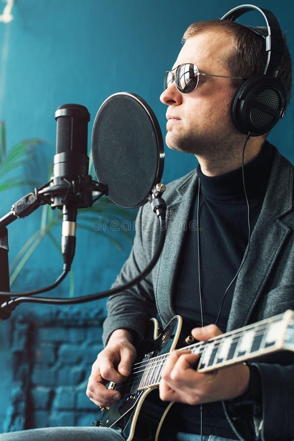 Cl?turez d'un chanteur d'homme reposer sur un tabouret dans des ?couteurs avec une guitare enregistrant une voie dans un studio ? images libres de droits