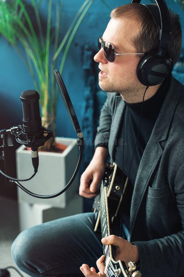 Cl?turez d'un chanteur d'homme reposer sur un tabouret dans des ?couteurs avec une guitare enregistrant une voie dans un studio ? photographie stock libre de droits