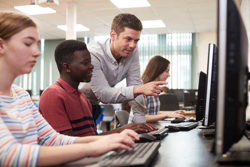 Cla de Working In Computer do estudante da escola de Helping Male High do professor fotos de stock royalty free