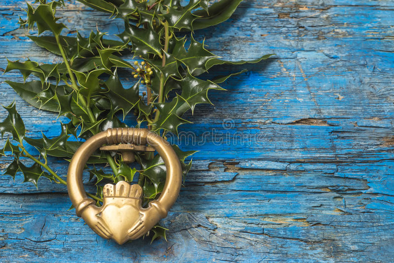 Claddagh and holly branches irish symbol of love. Friendship and loyalty in old wooden background royalty free stock image