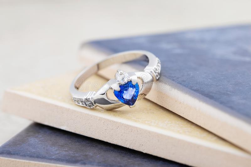 Claddagh ring with blue topaz. Traditional Irish ring in shape of two hands holding a heart shaped blue gemstone which represents love, loyalty, and friendship royalty free stock photos
