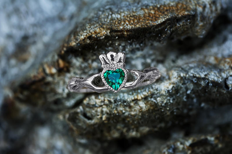 Claddagh ring with emerald heart. The Claddagh ring is a traditional Irish ring given which represents love, loyalty, and friendship royalty free stock image