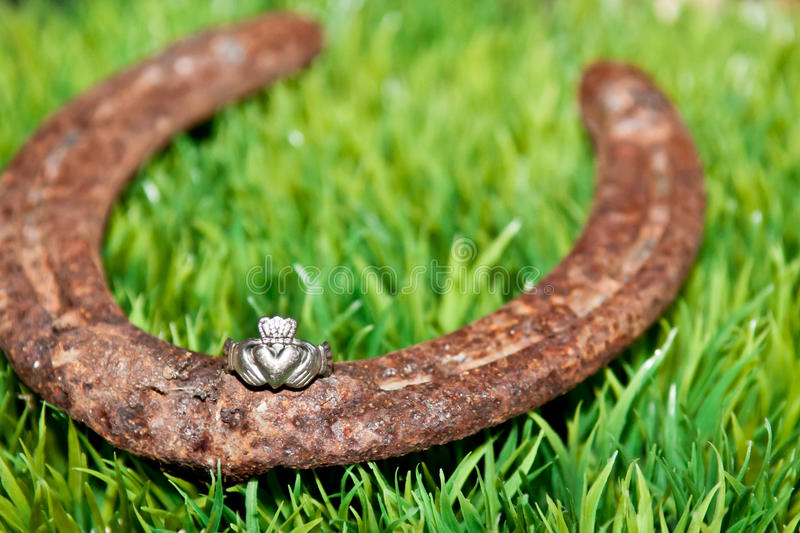 Claddagh ring and a Horseshoe. A Claddagh ring and horseshoe on grass stock images