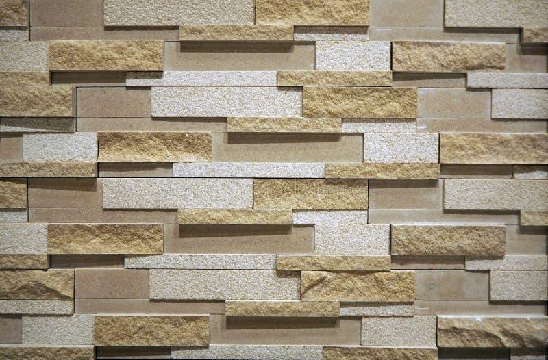 Cladding för stenvägg för inre som göras av staplade tegelstenar av den naturliga stenen Färg är skuggor av brunt royaltyfri bild